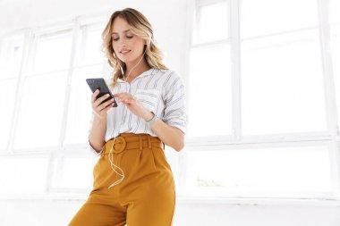Beautiful young blonde woman wearing shirt listening to music