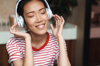 Portrait of pretty asian woman listening to music with headphone