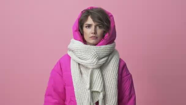 Nespokojená mladá žena v zimní bundě se šátkem dělá palec dolů gesto izolované přes růžové pozadí