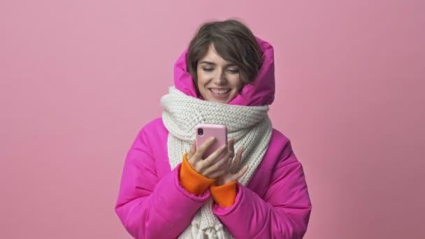 Atraktivní mladá žena v zimní bundě se šátkem je pomocí smartphone izolované přes růžové pozadí