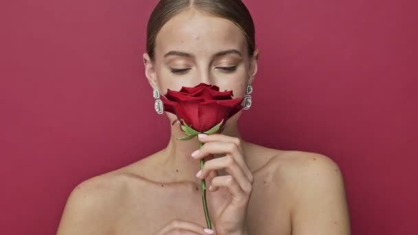 Attractive young woman with red lipstick and earrings smells the scent of a  red rose flower isolated over red background