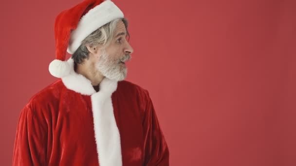 Atraktivní šedovlasý vousatý muž v kostýmu Santa Clause, dívající se stranou a ukazující něco s prázdnýma rukama oddělenýma přes červené pozadí ve studiu