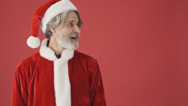 Překvapený šedovlasý vousatý muž v kostýmu Santa Clause ukazující na stranu a ukazující palec nahoru izolovaný nad červeným pozadím ve studiu