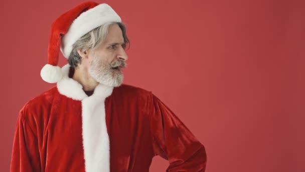 Atraktivní starší šedovlasý vousatý muž v kostýmu Santa Clause, který se poprvé dívá stranou s negativními výrazy a pak se podruhé dívá stranou s pozitivními emocemi izolovanými nad červeným pozadím ve studiu
