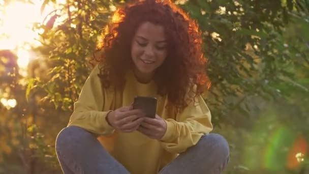 hübsche junge Frau mit lockigen rothaarigen Haaren, die im grünen Park sitzt und ihr Smartphone benutzt