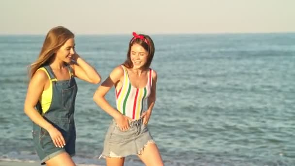 Attractive young girls talking to each other and laughing while walking along the beach in summer