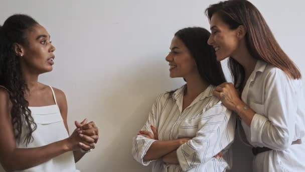 Three pleased young beauty women colleagues discussing while standing near the wall at office