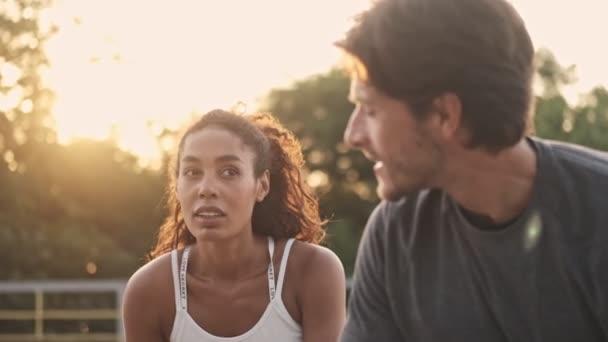 Klidný pár muž a žena ve sportovním oblečení při pohledu na sebe při odpočinku během cvičení na hřišti venku