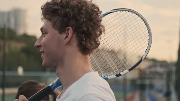 Boční pohled na veselého kudrnatého tenistu držícího tenisovou raketu a kráčejícího se svou soupeřkou na tenisovém kurtu