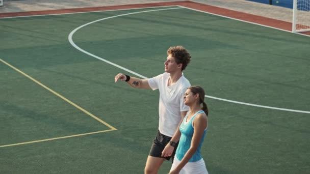 Boční pohled na Happy kudrnatý mužský tenista ukazuje pryč a mluvit se svou ženskou soupeřkou při chůzi společně na sportovním hřišti