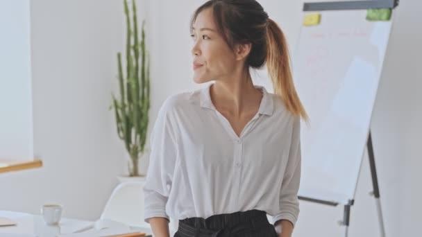Usmívající se mladá asijská obchodní žena stojí v bílé kanceláři při pohledu na stranu
