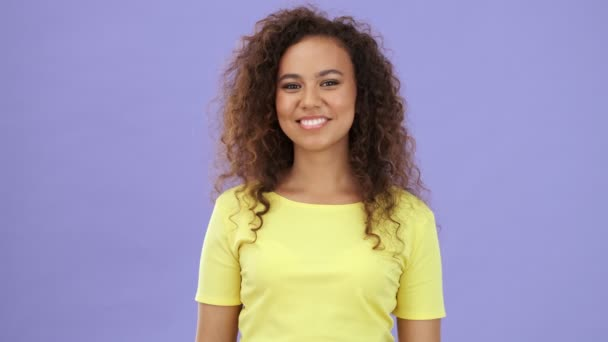 Charming happy african young woman in yellow t-shirt laughing while over purple background isolated