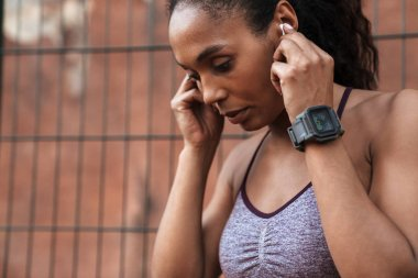Image of african american woman listening to music with earbuds