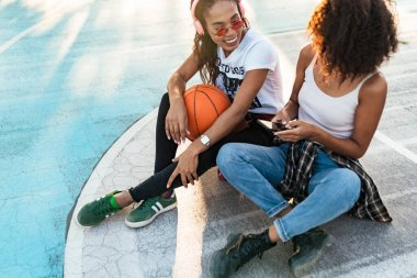 Image of african american girls sitting on playdround with baske