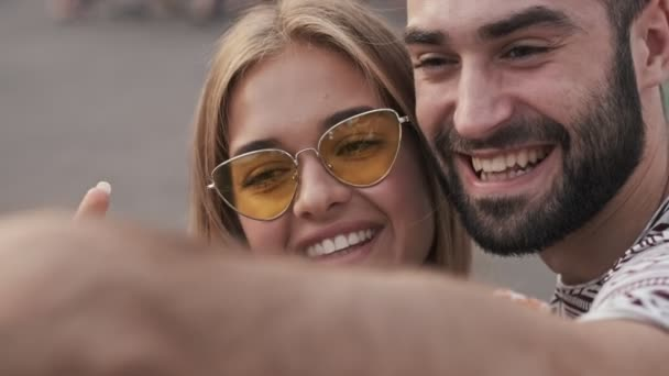 Positive couple man and woman are taking a selfie outdoors in an amusement park