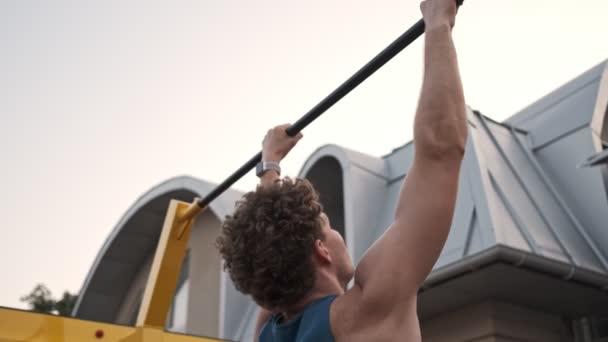 Soustředěný mladý kudrnatý muž dělá sportovní cvičení horizontální bar venku