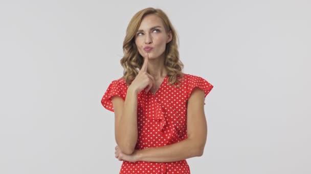 nachdenkliche hübsche blonde Frau im Kleid, die mit dem Finger am Kinn über etwas nachdenkt und glücklich wird, während sie danach vor grauem Hintergrund eine Idee hat