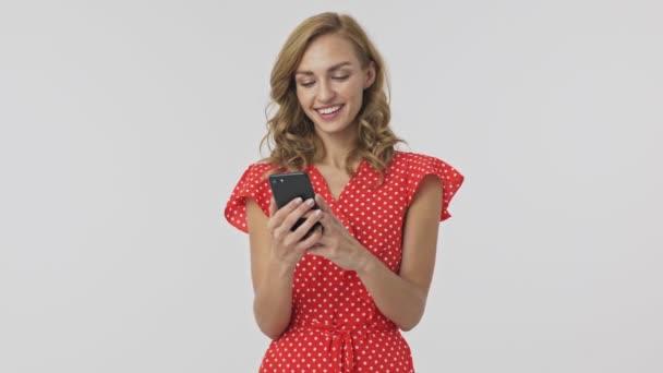 glückliche hübsche blonde Frau im Kleid mit Smartphone vor grauem Hintergrund