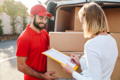 Photo Image of cheerful delivery man giving order to caucasian woman