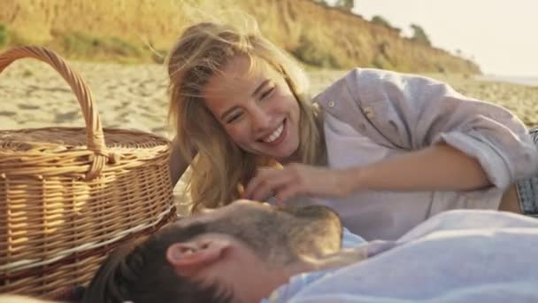 Attractive young couple man and woman are enjoying themselves while lying at the beach by the break of day