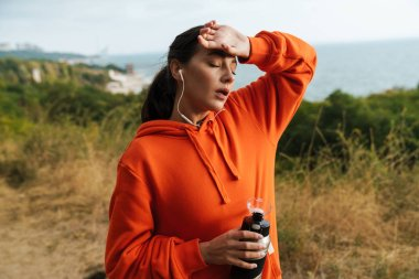 Photo of tired athletic woman using earphones and holding water bottle