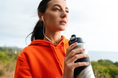 Photo of nice athletic woman using earphones and drinking water