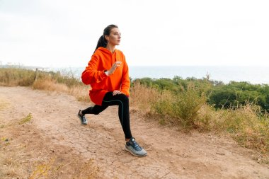 Photo of nice athletic woman using earphones and doing exercise