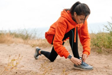 Photo of nice athletic woman using earphones and tying her shoelaces