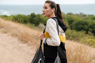 Photo of nice brunette woman using earpods while working with bag