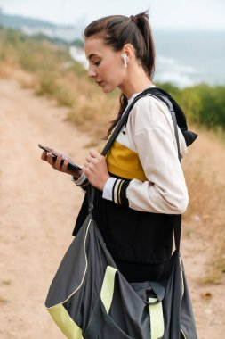 Photo of nice brunette woman using earpods and cellphone while working