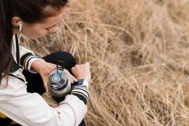 Cropped photo of nice brunette woman using smartwatch and holing bottle