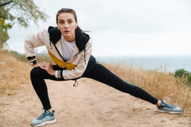 Photo of nice athletic woman using earpods and doing exercise