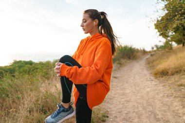 Photo of beautiful athletic woman using earphones and doing exercise