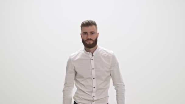 Egy jóképű, fiatal, szakállas férfi fehér ingben sétál a kamera felé, elszigetelve a fehér fal hátterétől.