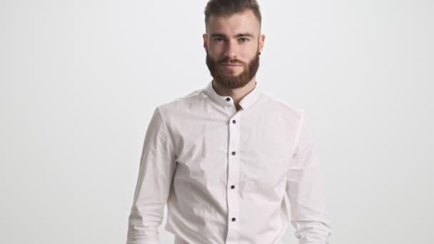 Hezký mladý vousatý muž se usmívá izolované přes bílou zeď pozadí