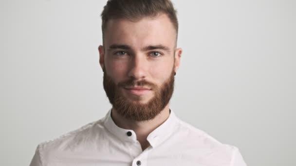 Klidný mladý vousatý muž v bílé košili zvedá oči ke kameře izolované přes bílou zeď pozadí