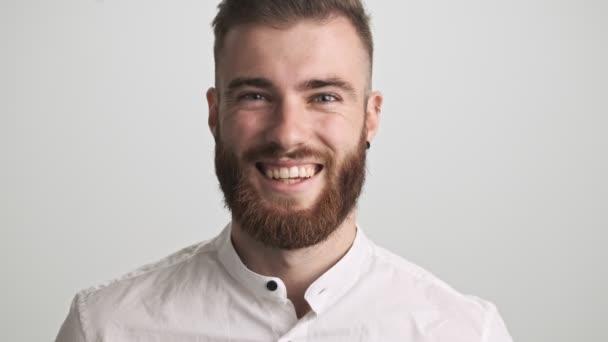 Pozitivní šťastný vousatý muž v bílé košili se směje při pohledu na kameru izolované přes bílou zeď pozadí