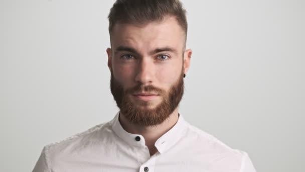 Klidný vousatý muž v bílé košili otvírá oči do kamery izolované přes bílou zeď pozadí