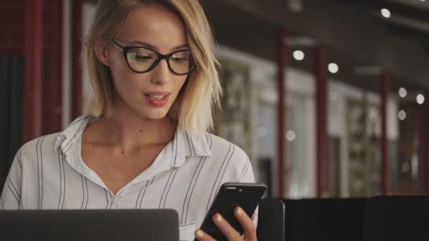 Smějící se mladá žena s brýlemi používá notebook a mobil, zatímco sedí v konferenčním sále