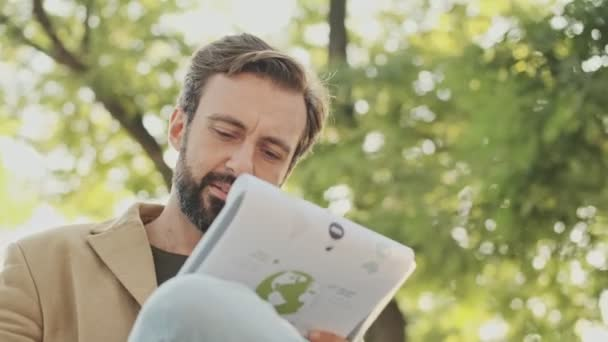 Pleased elegant bearded man in coat reading documents in clipboard while sitting in the park outdoors