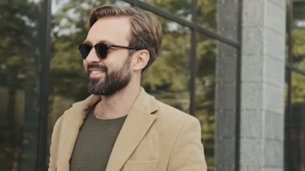 Happy elegant bearded man in coat and sunglasses looking away while walking outdoors