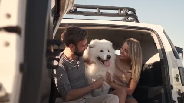 Usmívající se pár muž a žena se objímají a hladí psa, zatímco sedí v kufru auta