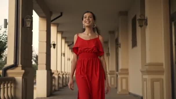 Egy gyönyörű, piros ruhás fiatal nő sétál a kamera felé az oszlopsorok közelében.