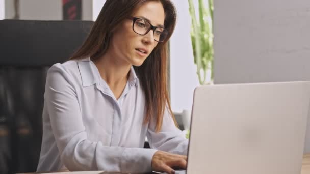 Concentrated businesswoman wearing eyeglasses working with documents and laptop computer while sitting in office