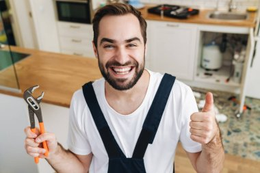 Image of young emotional happy man plumber work in uniform indoors holding pipe wrench showing thumbs up.