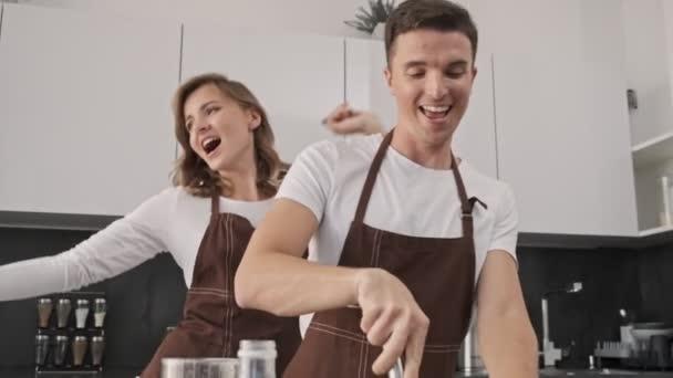 Positiv lächelndes junges Paar, Mann und Frau in braunen Schürzen, backen Teig, während sie in der Küche tanzen