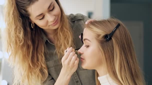 A side view of a professional makeup artist is applying mascara to the young beautiful blonde womans eyes at a beauty salon