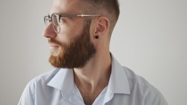 Usmívající se pozitivní radost mladý vousatý muž v brýlích otáčí tvář ke kameře izolované přes bílé pozadí