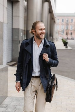 Attractive happy young bearded businessman walking outdoors in the street, carrying briefcase