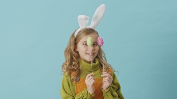 Funny young girl with blond hair and bunny ears plays with Easter eggs while looking at the camera isolated over blue background